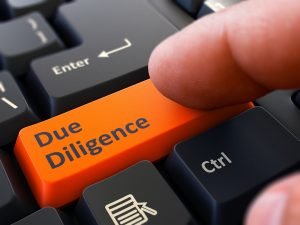 45139267 - due diligence - written on orange keyboard key. male hand presses button on black pc keyboard. closeup view. blurred background.
